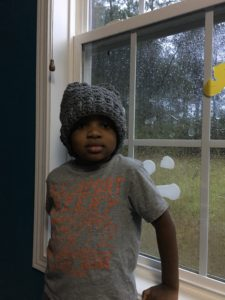 A young male boy standing in front of a window on a rainy day. He is wearing a gray, slouchy crochet hat.