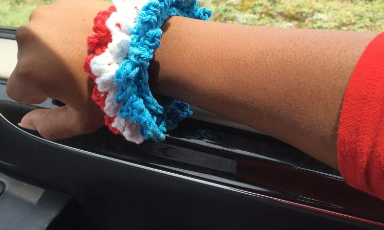 The Patriotic Bracelet is made with worsted weight cotton yarn in just 30 minutes! Learn how to make the chain loop stitch with this crochet accessory.