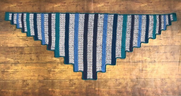 A flat lay of a triangular shawl made with alternating sections of solid color and lacy stitches.
