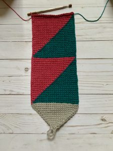 Crochet color block piece laying flat with a crochet hook.