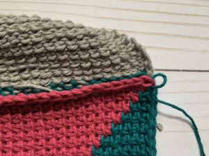 A close up picture of a yarn loop related to the instructions written before the picture.