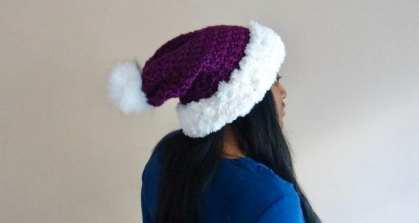 A picture of a royal purple crochet hat with a white faux fur pom and white faux fur edging on a woman with long, black hair.